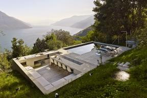 Terasa svenkovní kuchyní abazénem je obklopena zjedné strany zelení azdruhé velkolepým prostorem zakončeným siluetou Alp.
