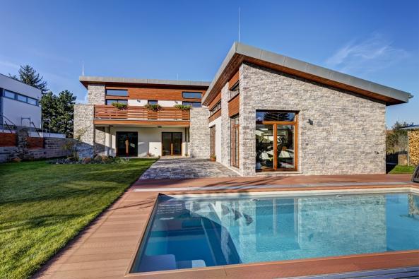 """Díky uspořádání domu doL vznikl nazahradě intimní prostor sotevřenou ikrytou terasou, přímo přístupný ze všech místností. Umístění bazénu bylo pečlivě promyšleno tak, aby nerušil hlavní výhled zobývacího pokoje. Architektonicky zajímavým prvkem jsou """"dvojúrovňová"""" okna, která mají významný efekt zejména vinteriéru."""