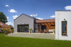 Dvě hmoty odlišené barevností fasády itvarem střechy spojuje dojednoho objektu komunikační krček obložený dřevem. Vnější rozdílnost domu se propisuje dointeriéru azdůrazňuje rozdílnost dvou obytných zón – intimní aspolečenské. Záměrem autorky projektu, architektky Heleny Paz, bylo navrhnout zvnějšku izevnitř srozumitelný dům.