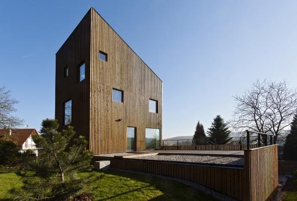 Nepravidelný obklad znehoblovaných latí odpovídá pojetí domu jako věže  akoresponduje svysokými štíhlými kmeny jehličnatého lesa zadomem.