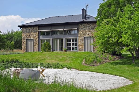 Jižní průčelí domu působí díky symetrickému řešení monumentálním dojmem. Ústřední prosklená plocha dosahuje přes galerii až dodruhého podlaží. Vpostranních  kamenných stěnách jsou dvoje dveře spojující zahradu  skrytou terasou astechnickým zázemím.