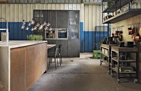 Dvířka spovrchovou úpravou zcementové stěrky, plechu sčernou nebo rezavou patinou vyzařují ducha starých dílen. Kuchyň Factory, výrobce Aster Cucine.