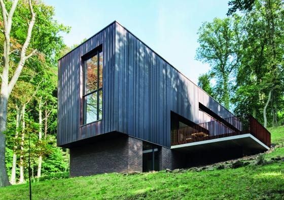 Budova je strukturovaná kolmo ke svahu a fyzikálně i opticky zasazena do terénu. Fasádní panely z mědi charakterizuje přirozená matně hnědá patina. (Zdroj: Schüco)