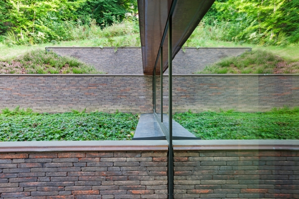 Na severní straně definují jednotlivé úrovně budovy cihlové zdi, korespondující stoupající terén. Velký podíl denního světla vstupuje do podzemního podlaží skrze sloupko-příčkovou fasádu ze systému Schüco ( AWS 75.SI) (Foto: Laurent Brandajs)
