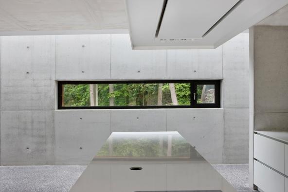 Pohledový beton je dominantním prvkem interiérového designu. Vidět je z části otvíravý okenní element ze systému Schüco AWS 75.SI. (Foto: Laurent Brandajs)