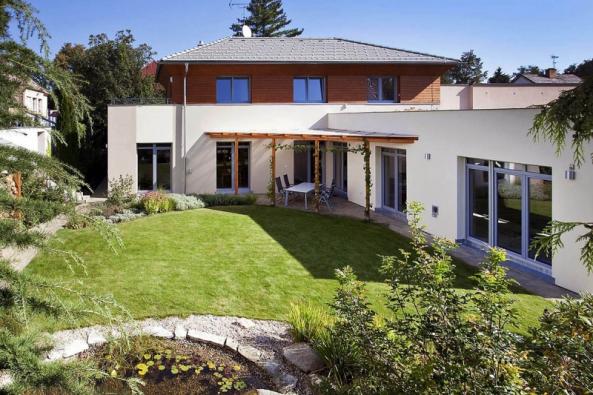 Rodinná vila vKolíně vkombinaci ploché avalbové střechy. Plochá střecha má vegetační úpravu – je nani vidět zoken ložnic vpatře.