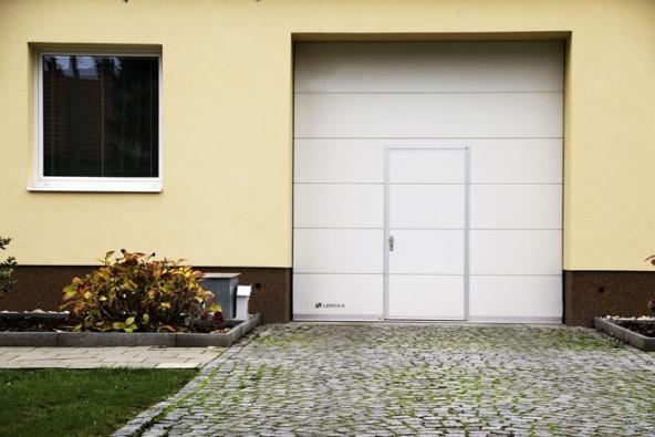 Garážová vrata Lomax Delta se skládají zněkolika panelů (sekcí), které se zapomoci torzních pružin pohybují vodicími kolejnicemi. Nasnímku sintegrovanými dveřmi.