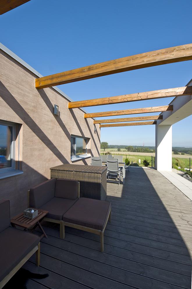 Probarvená strukturovaná omítka kontrastuje s bílým rámem stavby a dřevěnou pergolou.