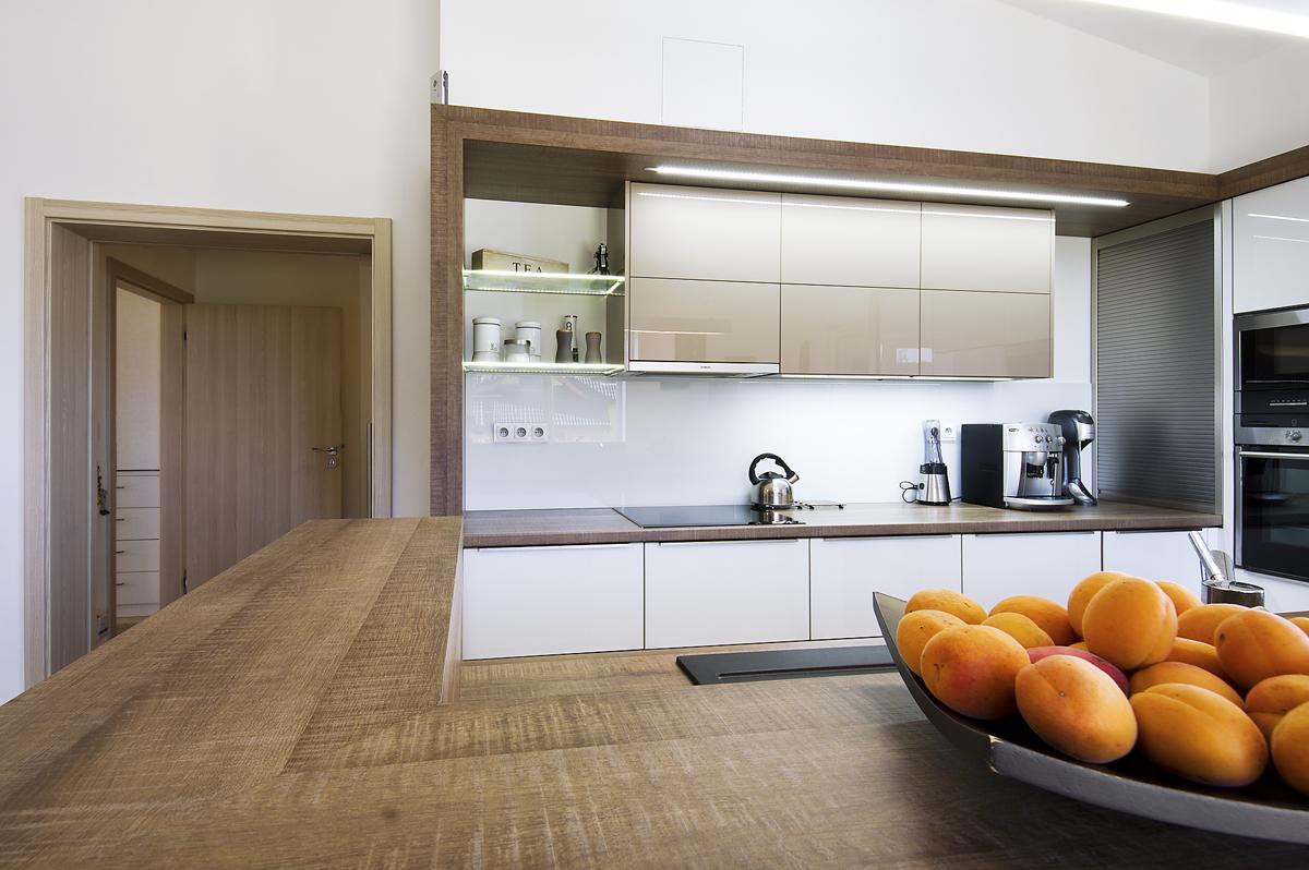 Kuchyňská linka dotváří společenské centrum domu a využívá stejné barevnosti i optických prvků kontrastního rámování.
