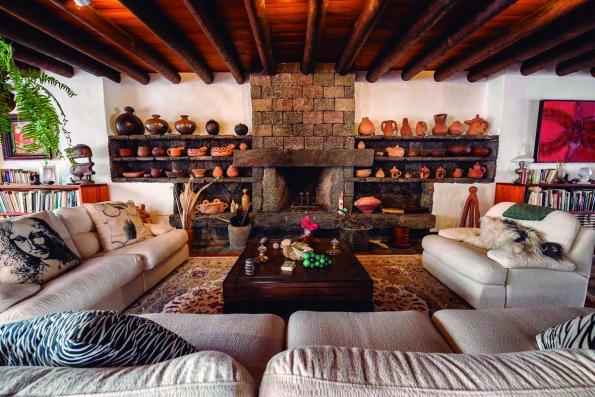 Obývacímu pokoji vévodí mohutný krb z basaltu s výstavou tradiční keramiky. Dřevěný strop s kulány je pro místní lidovou architekturu charakteristický. (Casa-Museo César Manrique Haría, Fotógrafo: Raúl Mateos, © Fundación César Manrique)