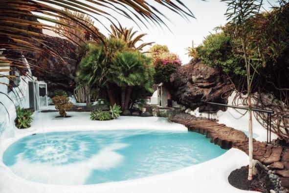 Sladká voda je na Lanzarote vzácná. Umělé jezírko vyhloubené v lávovém podloží skvěle osvěžuje klima, v pozadí je sezení a venkovní krb (Fundación César Manrique, Tahíche, Fotógrafo: Raúl Mateos, © Fundación César Manrique)