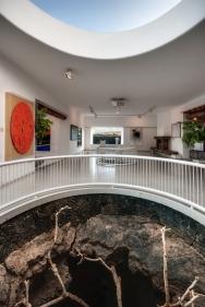 """Výstavní prostory Mistrovy nadace se nacházejí v horní části domu, která je velkými okny působivě propojena s okolní krajinou a otvory v podlaze s obytnými bublinami v lávovém """"podsvětí"""". (1) (Fundación César Manrique, Tahíche, Fotógrafo: Raúl Mateos, © Fundación César Manrique)"""