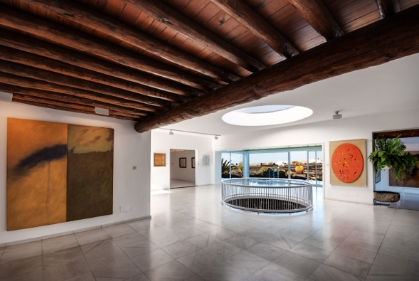"""Výstavní prostory Mistrovy nadace se nacházejí v horní části domu, která je velkými okny působivě propojena s okolní krajinou a otvory v podlaze s obytnými bublinami v lávovém """"podsvětí"""" (2) (Fundación César Manrique, Tahíche, Fotógrafo: Raúl Mateos, © Fundación César Manrique)"""