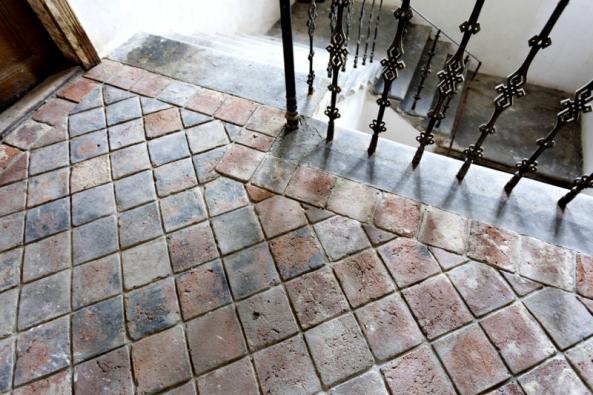 Naschodiště navazuje vprvním patře podlaha ze starých použitých půdovek. Pálená hlína je nedostižný materiál, ale je třeba ještě půdovky ošetřit proti otěru.