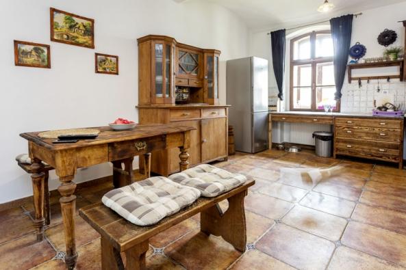 Jídelní stůl vkuchyni, vpravo je vidět stará kredenc ačást pracovní plochy kuchyňské linky. Vtéto místnosti zapůsobení JZD probíhal  chov kachen.