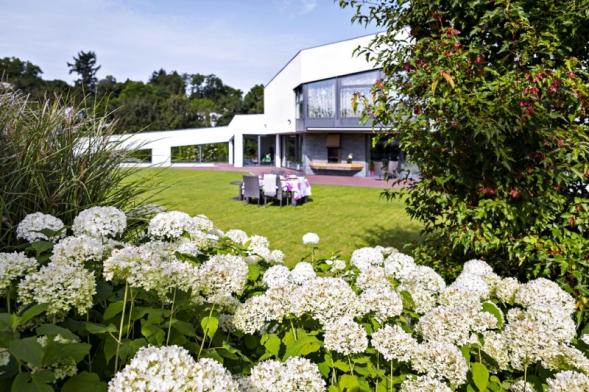 Vzahradě se spojují dvě témata – pravidelnost architektury avenkovské prostředí. Kombinujeme tradiční zahradní druhy sdivočejšími směsmi trvalek, zeleň je však vedena vpravidelném tvaru.