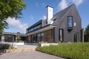 Protáhlý obdélníkový tvar, výrazná sedlová střecha avysoký komín představují tradiční znaky anglických venkovských domů. Horizontální vikýř, přesahující stropní desky avelké nečleněné prosklené plochy bez rámů hovoří jazykem současné architektury.