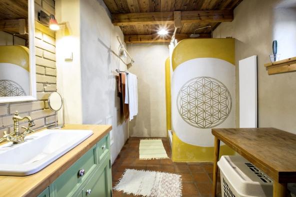V koupelně nás zaujala podlaha z půdovek, nádherný trámový strop a příjemně zaoblené hrany hliněných omítek. Na spodním obrázku vidíte mozek fotovoltaické elektrárny a baterie.