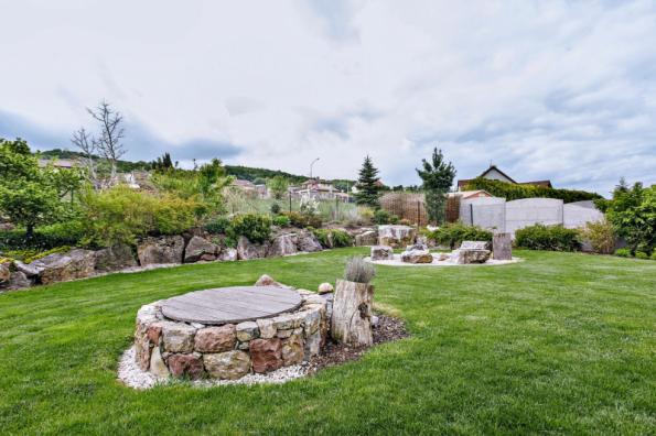 Místní kámen hraje v této zahradě hlavní roli. Ať už jako originální posezení u ohniště, nebo jako obložení krytu studny. ...Okrasné výsadby v budoucnosti zakryjí nevzhledné betonové oplocení sousedního pozemku.