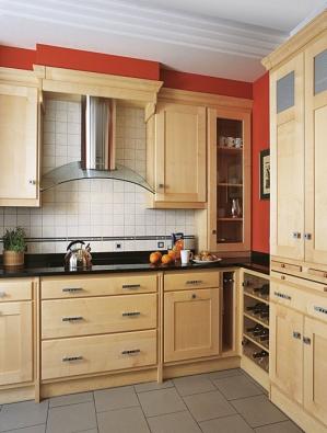 Kuchyňský nábytek vyrobený zjavorového dřeva, které je ponecháno vpřírodním tónu. Odlehčený vzhled kuchyně umocněný použitím odsávače vkombinaci nerezu askla zapracovaného dovestavby.