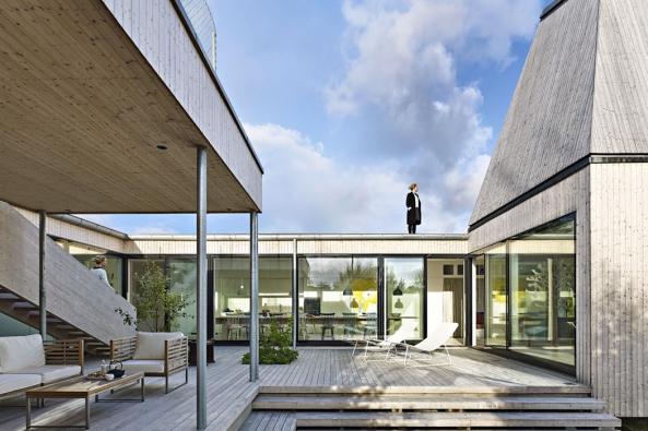Dřevěný dům je zvenčí pevností oddělující své obyvatele odsousedních domů auvnitř otevřeným členitým prostorem, kde se stírají hranice mezi exteriérem ainteriérem.