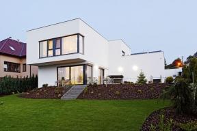 Hlavní obývací prostory v domě jsou orientovány do zahrady a bohatě prosvětleny velkými rohovými prosklenými plochami. Horní podlaží přesahuje přes přízemí a stíní jej proti západnímu slunci. Jižní okna jsou chráněna venkovními screenovými roletami.
