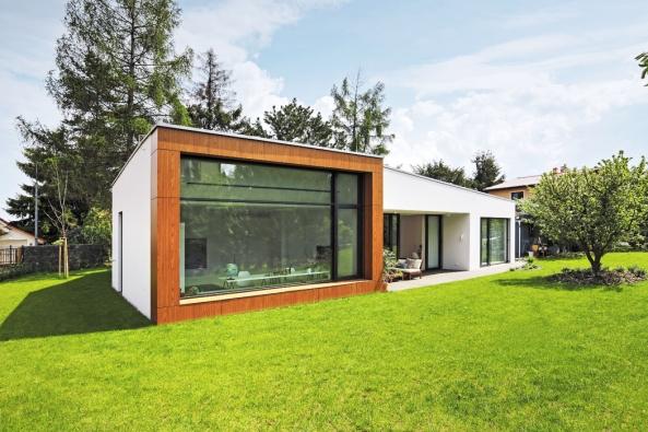 Fasáda rodinného domu otočená dozahrady používá jako dominantu velké okno. Jediná převýšená místnost je aktuálně určena dětským hrám.