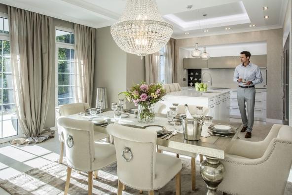 Přízemí je laděno dojemných světlých teplých tónů. Nafunkcionalistickou bílou kuchyň vevysokém lesku navazuje luxusní jídelní stůl se stříbrnou patinou ažidlemi spříjemným lněným čalouněním, jejichž oblé tvary přímo vyzařují měkkost apohodlí.