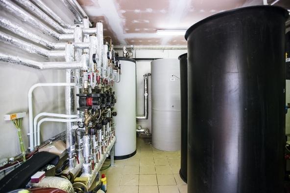 Voda, kterou tepelná čerpadla ohřejí, se shromažďuje vohromných zásobnících (vpravo) apotom je složitou sítí potrubí rozváděna dovšech budov vhotelovém areálu.