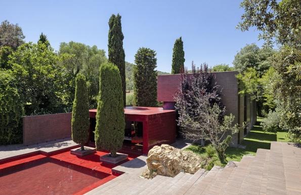 Tentýž dům zboční strany: hlavní jídelna je orientována kbazénu snetradiční červenou barvou obkladů. Dům santickou atmosférou integroval izbytky původní venkovské usedlosti.