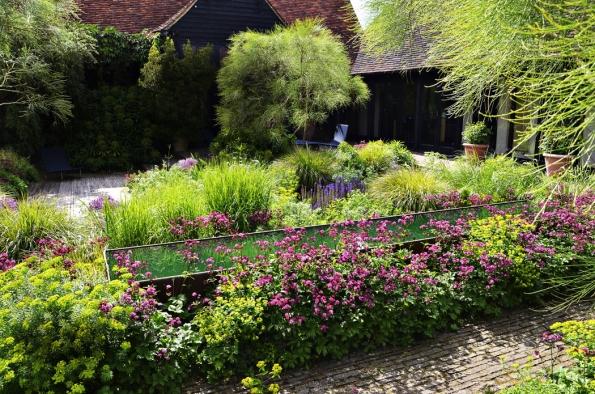 Malý dvorek je využívaný jako intimní rodinný prostor. Tlumená barevnost přirozeně zešedlého dřeva a starých cihel je doplněna výraznou barvou cortenu. Klidná hladina vodní nádrže zrcadlí nejen okolní rostliny, ale také mraky na obloze.