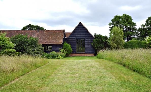 Černě natřená dřevěná fasáda je pro zemědělské stavby v této oblasti typická. Majitelé respektovali původní půdorys i výšku stavby, která do krajiny velmi dobře zapadá.