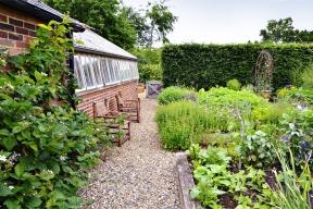 V užitkové zahradě je pravidelný půdorys vyvýšených záhonů zjemněn přesévajícími se letničkami. V ose cestičky je postavena nádoba s pnoucími hrachory. I tady je patrná ruka citlivého zahradníka.