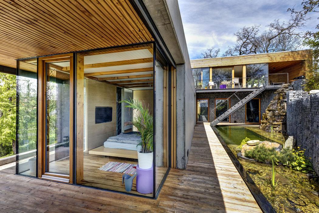 Prosklené fasády domu tvoří kombinace bezrámového zasklení avelkoformátových posuvných ploch vmasivních dubových rámech. Exteriér je tak maximálně propojen sinteriérem.