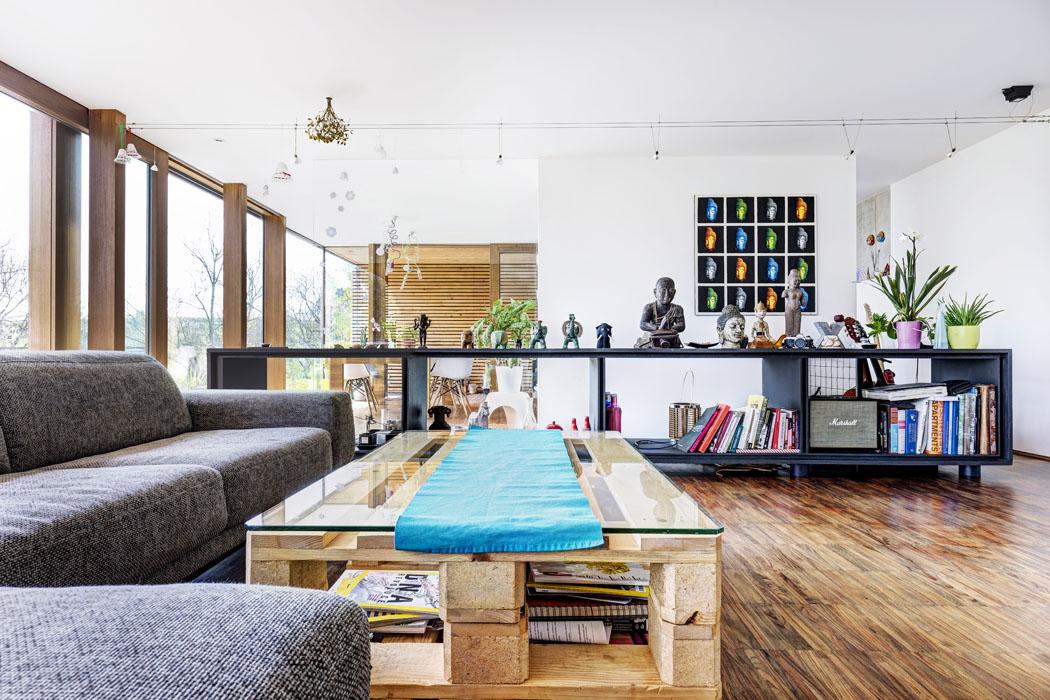 Společný obývací prostor je rozdělen nasezení akuchyňskou část, skrytou zapolopříčkou. Středem prochází schodiště ze spodního podlaží, lemované dlouhou otevřenou skříňkou zMDF desek ačerného ocelového plechu.