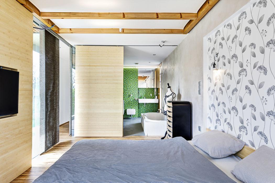 Ložnice rodičů vjaponském stylu: posuvné dřevěné stěnové prvky, zavěšené nastropních kolejničkách, slouží kinstalaci televizoru akoddělení koupelny. Doplňují je posuvné textilní pruhy sloužící kzastínění.