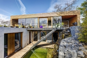 Každý, kdo se někdy zajímal omoderní architekturu ajejí historii, nemohl nenarazit napověstnou Vilu nad vodopádem, jejímž autorem je slavný americký architekt Frank Lloyd Wright. Srovnání snovostavbou naokraji Prahy je možná trochu zavádějící, nicméně ivtomto případě vzniklo vobtížných terénních podmínkách pohodlné moderní bydlení, kde se vstává iusíná smelodií padajícího proudu vody.