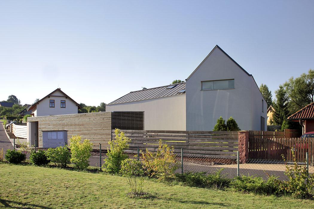 Ze štítu je patrný tradiční profil domu se sedlovou střechou. Ten prochází nad celým půdorysem, ale plynule se snižuje výška hřebene střechy. Doulice se tak obrací dvoupodlažní dům, dozahrady přízemní domek. Kompaktní forma bez střešních přesahů odpovídá současnému modernímu pojetí venkovské zástavby.
