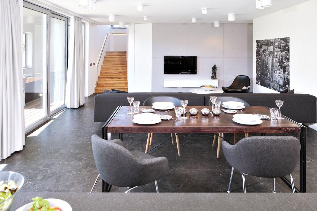 Velkorysý společný obývací prostor má vinylovou podlahu imitující nerez plech.