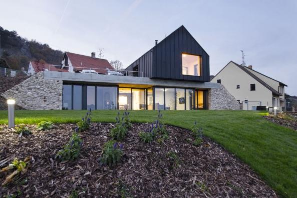 Při pohledu zdálky dům tvarově splývá sokolní zástavbou, přesto klasické venkovské stavení naprvní pohled zaujme jednoduchou formou sčerným pláštěm. Zuliční úrovně by pod čistou linií stavby nikdo nehledal obytné podlaží zahloubené dosvažité zahrady. Dvě přes sebe přeložené hmoty objektu vyšly tvořivým způsobem vstříc požadavkům investorů ináročným pravidlům CHKO.