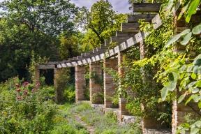 Oválnou pergolu zpálených cihel adřevěných trámů zdobí sbírka pnoucích růží rozmanitých barev avůní. Romantickou náladu podtrhují pěšiny lemované aromatickými bylinami.