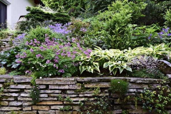 Terénní převýšení zde vyřešily kamenné zídky, které navíc do zahrady skvěle zapadají a neruší tak její přírodní charakter.