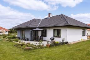 Po obvodě celého domu je patrný zvětšený přesah střechy, který chrání stěny před deštěm, zároveň stíní prosklené plochy, vchod do domu i prostor terasy před sluncem.