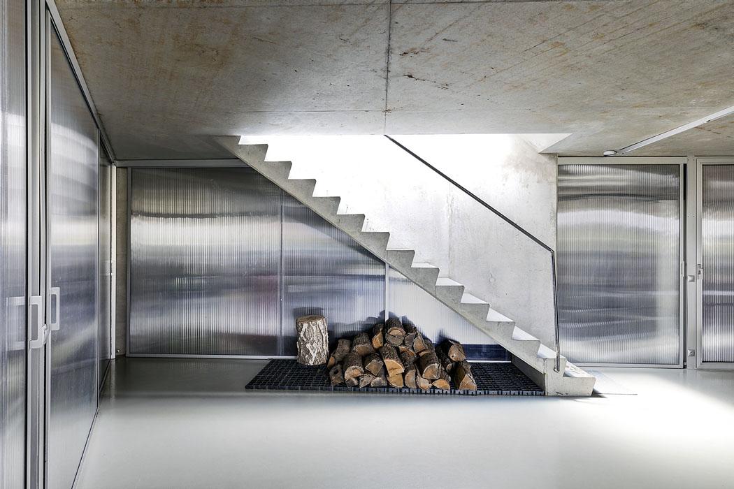 Z haly v suterénu vede otevřené schodiště přímo do společného obývacího prostoru. I zde mají havní slovo pohledový beton a sklo.
