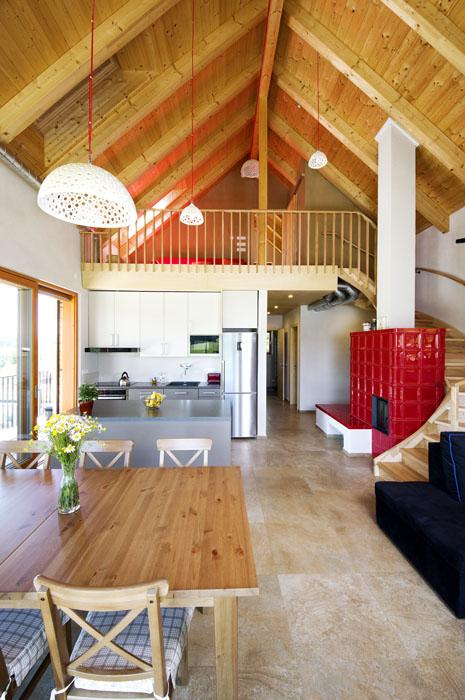 Hlavní obytná místnost otevřená do krovu spojuje kuchyni, jídelnu, obývací pokoj i galerii s pracovnou. Její dominantou jsou centrální kachlová kamna v sytě červené barvě.