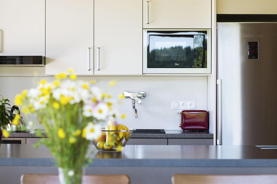 Horní část kuchyňské linky splývá s bílou omítkou, zatímco spodní skříňky odpovídají zemitému tónu keramické dlažby.
