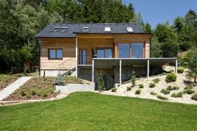 Jednoduchý obdélníkový tvar domu s velikým oknem na východ a s proskleným výklenkem orientovaným na jihozápad dává majitelům možnost sledovat krásné výhledy a měnící se krajinu při různém denním osvětlení.