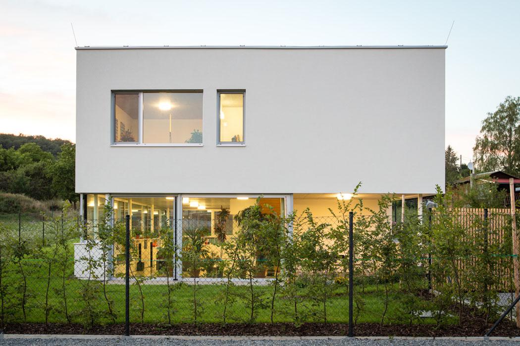 Prosklený dům kubických tvarů se zelenou střechou