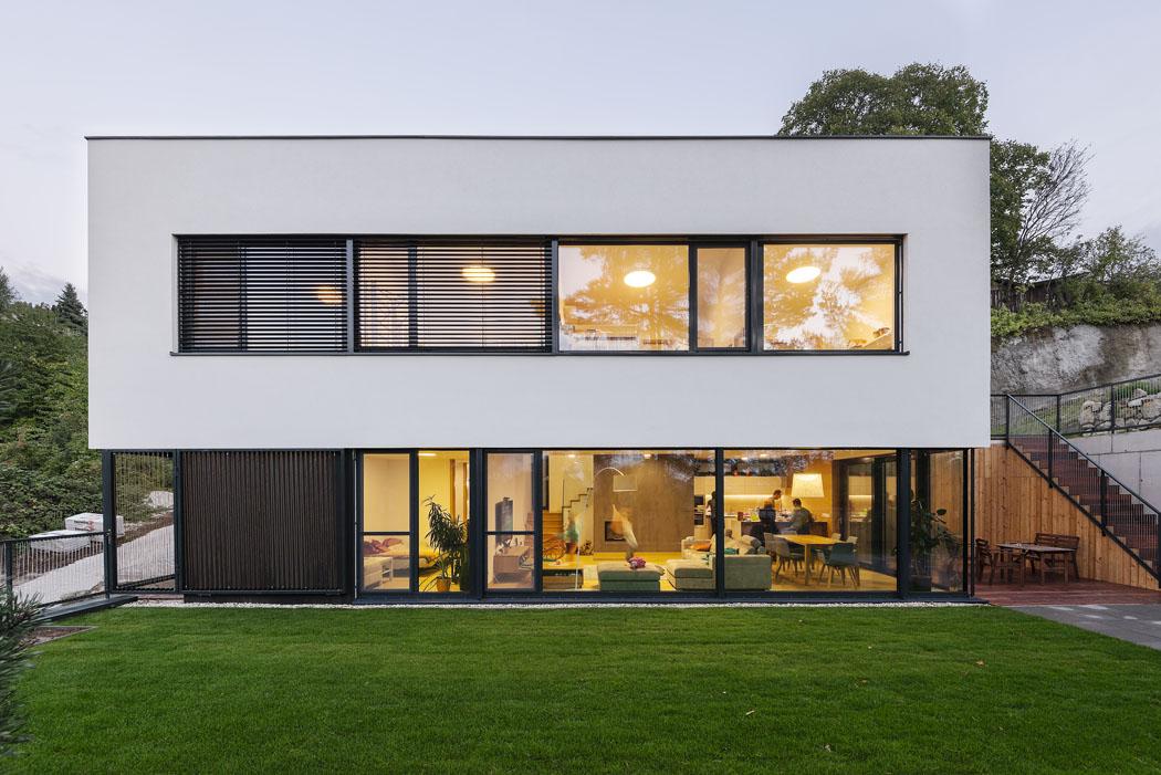 Působivým výtvarným prvkem je rastr okenních profilů kontrastující somítkou askleněnou plochou. Nápaditě přechází pofasádě až kevstupní brance aoplocení.