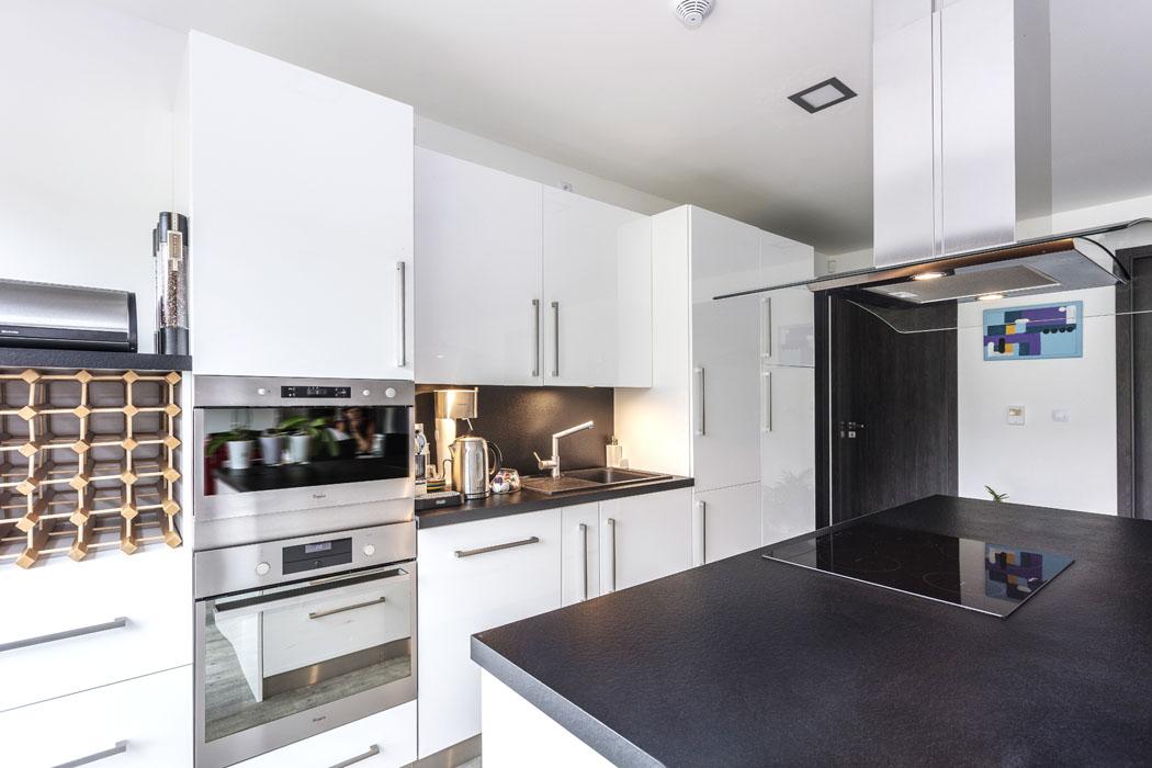 Fronta kuchyňského nábytku s povrchem v elegantní bílé barvě a kontrastně tmavou pracovní deskou je doplněna ostrůvkem s varnou deskou a digestoří v témže provedení.
